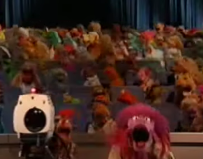 Clifford, a camera Muppet and camera in the foreground, various Muppets as audience in the background